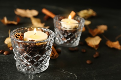 Glass holders with burning candles, coffee beans and cinnamon on black stone table, closeup. Space for text