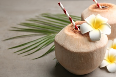 Fresh coconut with drinking straw and flowers on grey table, closeup. Space for text