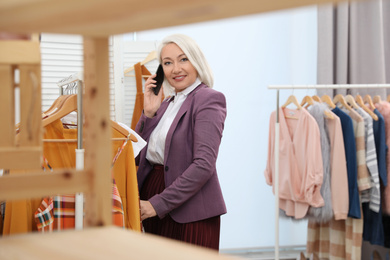 Female business owner talking on phone in boutique