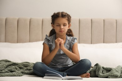Cute little girl praying over Bible in bedroom