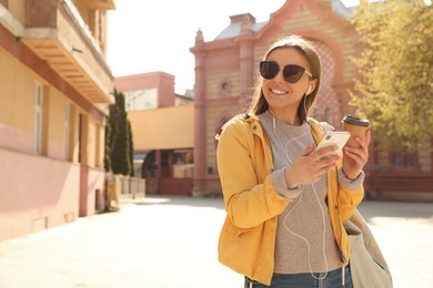 Happy young woman with coffee listening to music on city street in morning