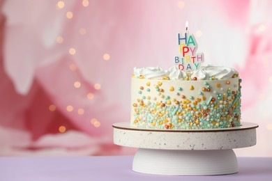 Beautiful birthday cake with burning candle on violet table. Space for text