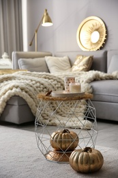 Cup of drink, burning candles and decorative pumpkins in living room. Interior design