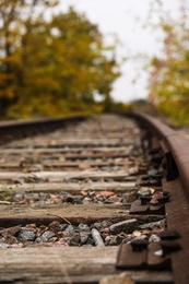 Railway line with track ballast in countryside, closeup. Train journey