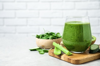 Delicious green juice and fresh ingredients on table against brick wall, space for text