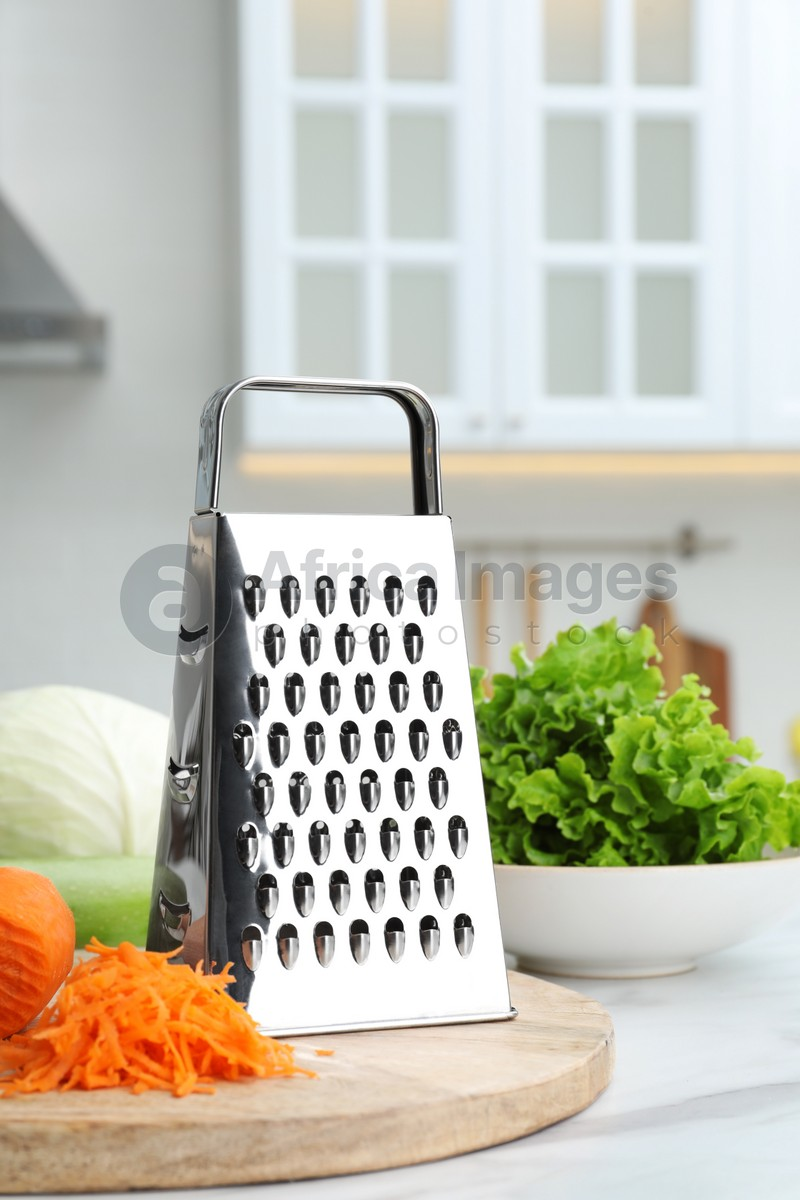 Grater and fresh ripe carrot on white table in kitchen