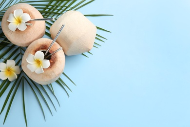 Fresh coconuts with drinking straws and flowers on light blue background, flat lay. Space for text