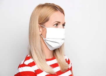 Woman wearing handmade cloth mask on white background. Personal protective equipment during COVID-19 pandemic