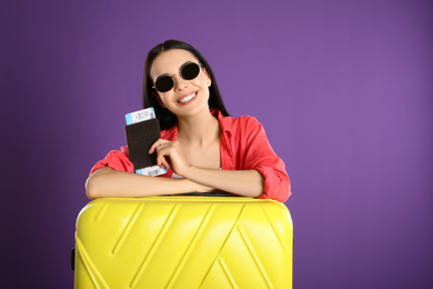 Beautiful woman with suitcase and ticket in passport for summer trip on purple background. Vacation travel