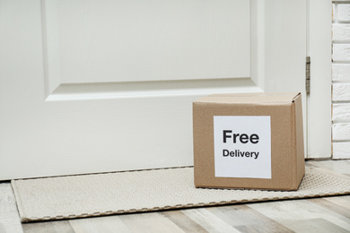 Parcel with sticker Free Delivery on rug indoors, space for text. Courier service