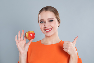Young woman with apple on grey background. Vitamin rich food
