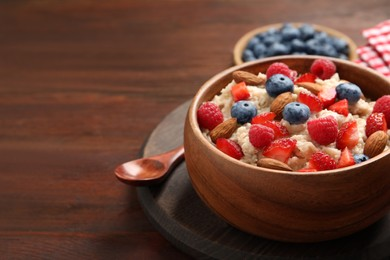Tasty oatmeal porridge with berries and almond nuts in bowl served on wooden table, space for text