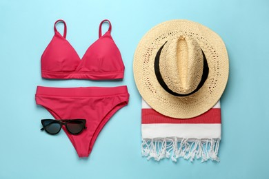 Flat lay composition with different beach objects on light blue background