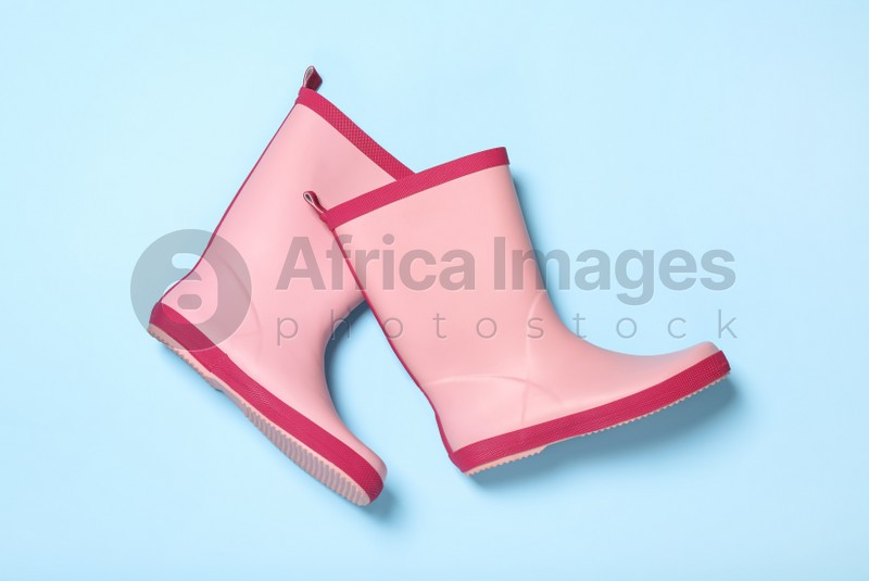 Pair of pink rubber boots on light blue background, top view
