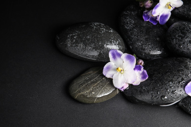 Stones and flowers in water on dark background. Zen lifestyle
