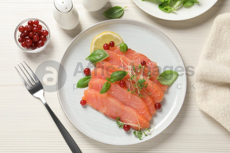 Delicious salmon carpaccio served on white wooden table, flat lay