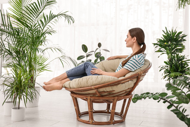 Young woman in room decorated with plants. Home design