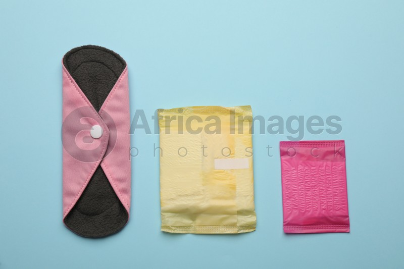 Disposable menstrual pads near reusable cloth one on light blue background, flat lay