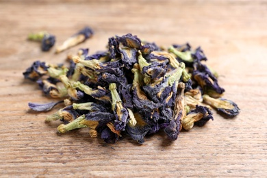 Pile of dry organic blue Anchan on wooden table, closeup. Herbal tea