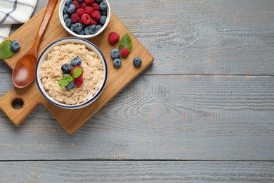 Tasty oatmeal porridge with berries on grey wooden table, top view. Space for text