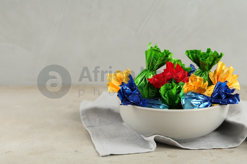 Candies in colorful wrappers on light beige table, space for text