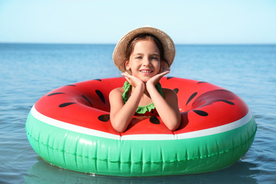 Cute little child with inflatable ring in sea on sunny day. Beach holiday