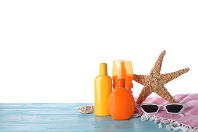 Sun protection products and beach accessories on blue wooden table against white background. Space for text