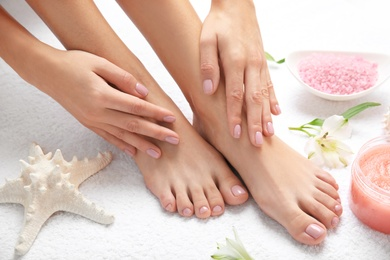 Cosmetic, flowers and woman touching her smooth feet on white towel, closeup. Spa treatment