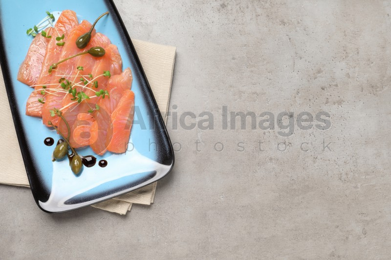 Delicious salmon carpaccio served on light grey table, top view. Space for text