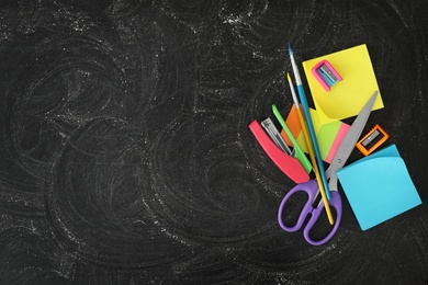 Different stationery on blackboard, flat lay with space for text. Back to school