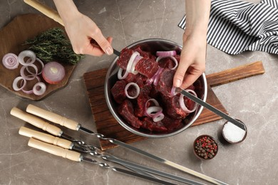 Woman stringing marinated meat on skewer at table, top view