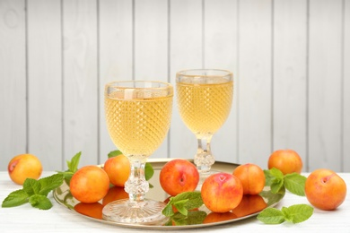 Delicious plum liquor, ripe fruits and mint on table against white background. Homemade strong alcoholic beverage