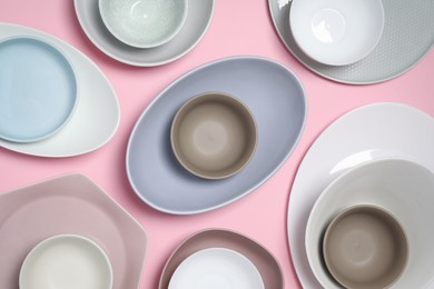 Different plates and bowls on pink background, flat lay