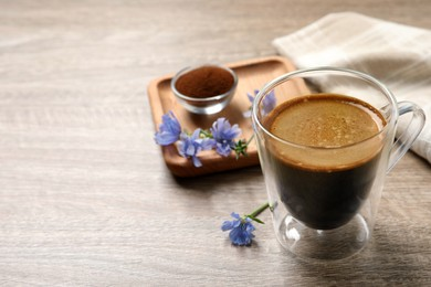 Glass cup of delicious chicory drink and flowers on wooden table, closeup. Space for text