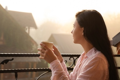 Young woman with cup of tea enjoying beautiful view in morning