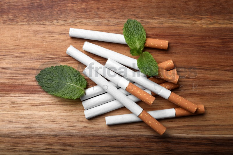Menthol cigarettes and mint leaves on wooden table, flat lay