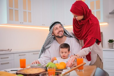 Happy Muslim family eating together in kitchen, space for text