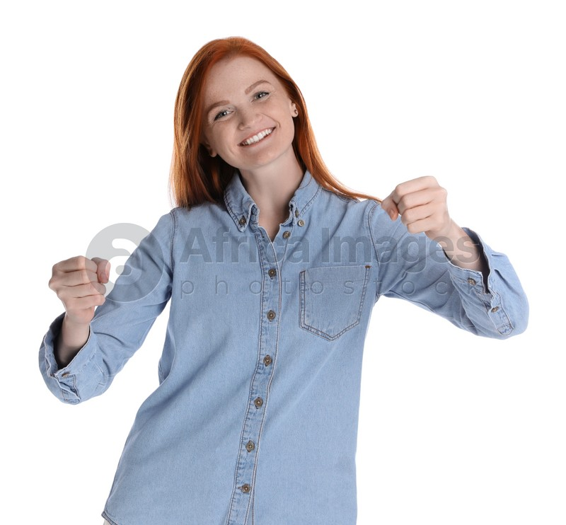 Happy young woman pretending to drive car on white background