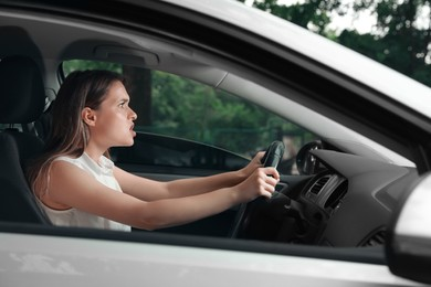 Stressed young woman in driver's seat of modern car