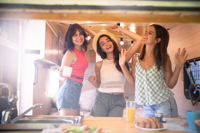 Happy young women dancing in trailer. Camping vacation