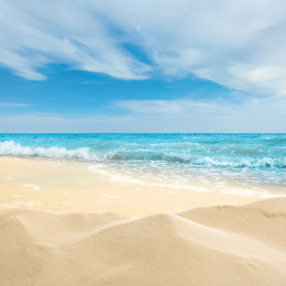 Ocean waves rolling on sandy beach under blue sky with clouds