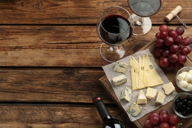 Tasty red wine and snacks on wooden table, flat lay. Space for text