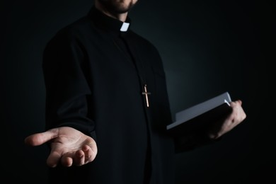 Priest with Bible praying on dark background, closeup