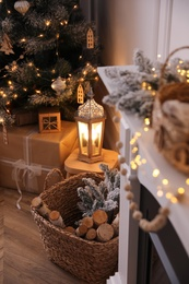 Basket with wood near fireplace and Christmas tree indoors. Interior element