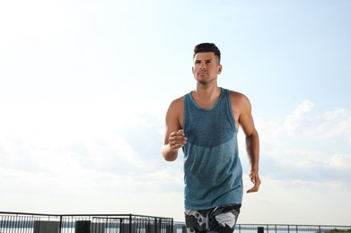 Handsome man in sportswear running outdoors on sunny day