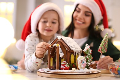 Mother and daughter decorating gingerbread house at table indoors