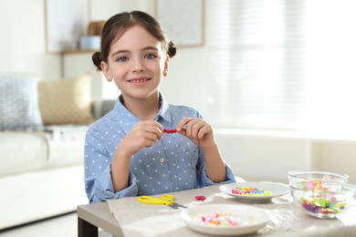 Little girl making accessory with beads at table indoors. Creative hobby