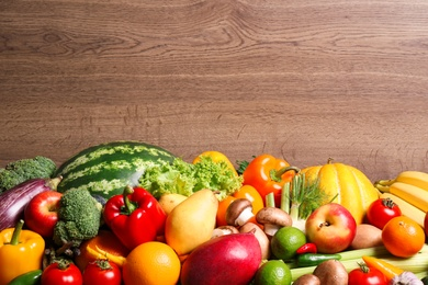 Assortment of fresh organic fruits and vegetables on wooden background, closeup. Space for text