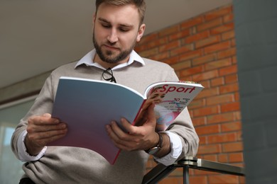 Young business man reading sports magazine indoors