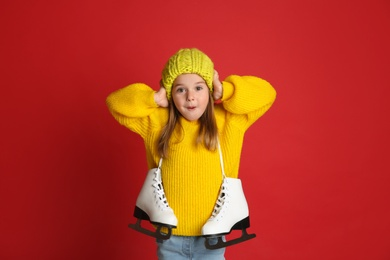 Excited little girl in yellow knitted sweater with skates on red background
